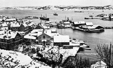 Sett fra Feierheia før 1920: Et gammelt postkort som butikken Kristiane Johnsen ga ut tidlig på 1900-tallet. På folkemunne ble butikken bare omtalt som Kissi Johnsen. Fotografiet viser at seilskutetiden er forbi og dampskipene kommer for fullt. Ved Dampskipsbrygga ligger en av kystrutas båter til kai. Dette er tidlig på vinteren, for det har ennå ikke kommet is på fjorden.