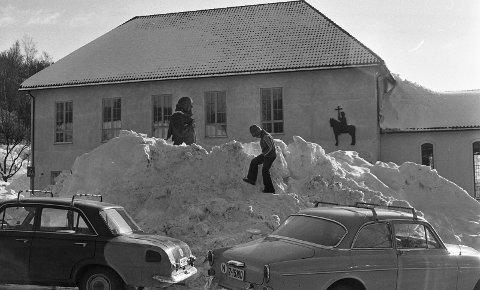 Ungene koser seg i snøhaugene på Landstads plass (1977