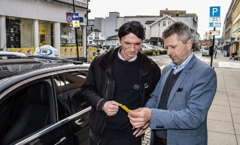DAGEN DERPÅ: Taxisjåfør Ali Berisha og Thomas Bjanger studerer boten på 900 kroner for episoden utenfor Gullsaksen Frisør i Storgata onsdag ettermiddag.