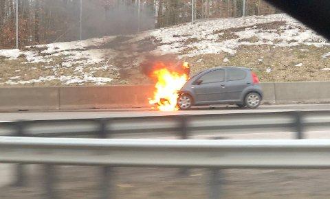 En bil begynte å brenne på motorveien ved Tassebekk.