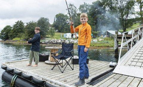 Fiskelykke: Marius Tingvoll (8) fra Rensvik skole og Ola Husby Mosand (19) fra Tingvoll barneskole kjente ikke hverandre før friluftsuka, men nå har de blitt de gode venner.