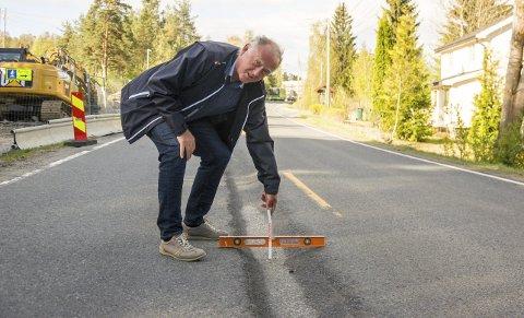 DÅRLIG OG FARLIG: Her måler Vidar Løvf sporene i Eikerveien til 10 centimeter. Nå forventer han at det snarest blir gjort noe.