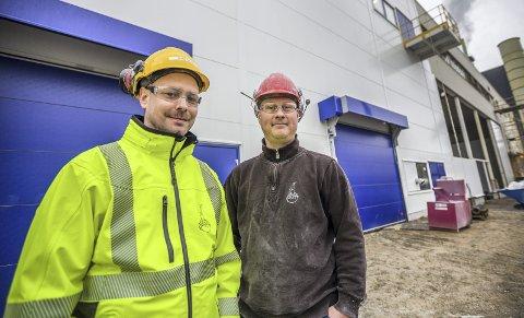 Tar i bruk ny teknologi: Produksjonssjef Glenn Østbye (38) (til venstre) og driftsassistent Jon Rasmussen (40) ved Kronos Titan foran nybygget på Øra til rundt 60 millioner kroner, inkludert nytt teknologisk utstyr. Rasmussen har vært delaktig i hele byggeprosessen. (Foto: Felix Ellingsrud)