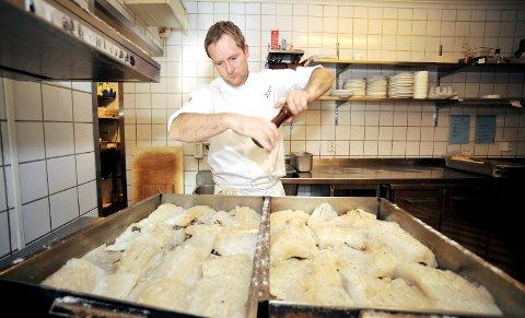 PEPPER: Det siste lutefiskkokk Eirik Storm Lillebø gjør før lutefisken skal inn i stekeovnen, er å kverne over sort pepper. Foto: Vidar Ruud, ANB