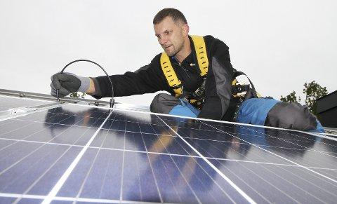 Monterer solcellepaneler: Montør Hubert Kojc fra Solcellespesialisten på taket i Hvittingfossveien som skal få strøm fra sola. Alle foto: Pål Nordby