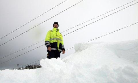 66.000 VOLT: Energimontør Øyvind Gundersen i Troms kraft nett drister seg ikke helt opp på toppen av snøhaugen. I kablene er spenningen 66.000 volt. Foto: Stian Saur