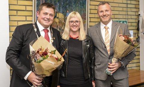 BLOMSTER: En smilende Anne-Nora Oma Dahle overrakt blomster til ordfører Halvor Homme og påtroppende varaordfører Geir Christian Enger. FOTO: NILS JUL LANDE