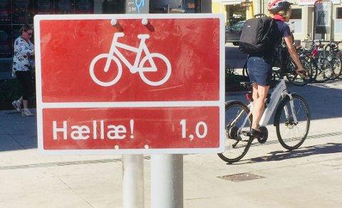 ÉN KILOMETER TIL HÆLLÆ? Dette skiltet på Stortorvet angir at det er én kilometer til Hællæ! Over hele distriktet er det nå satt ut humor-sykkelskilt for å skape  blest om Den nasjonale sykkelkonferansen om halvannen uke.