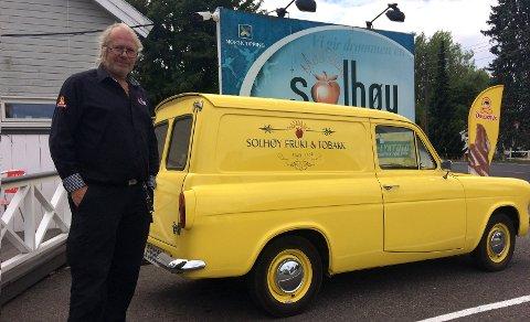 STOLT EIER: Lars-Petter Arnesen har brukt mye tid og penger på den gule Ford Anglia-modellen han har stående foran forretningen sin. Den er fra 1962, og har opplevd mye gjennom sin lange levetid.