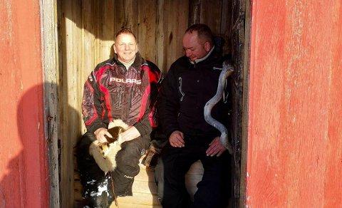 GODT I GANG MED PROSJEKTET: Stig Arvola kjøpte i 2018 den gamle skolen i Andersby for å restaurere og bruke plassen til blant annet konferanser og selskap, samt å formidle historie. Nå har han fått penger til å restaurere den gamle utedoen. Her sitter Arvola på utedoen i selskap med Odd Magne Wik.
