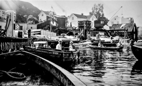 Legatbrygga på Øya: Et fotografi fra sent på 1960-tallet. Stedet er Marina Service på Øya, det som tidligere ble kalt for «Legatbrygga». En allmannabrygge nedenfor Legatets eiendommer. Som bildet viser var dette i brytningen mellom trebåter og plastfartøyer. I bakgrunnen kommer en pram med en liten påhengsmotor. Før Marina Service var det et kull- og vedlager på denne brygga
