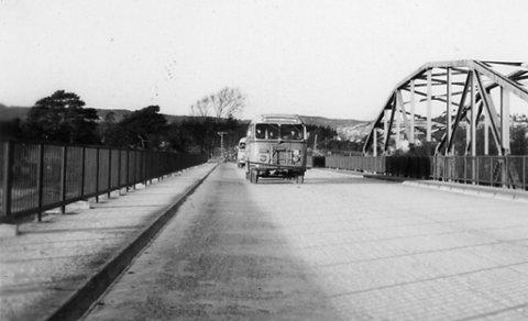 Første buss: Rekkeviksbussen med Fritz Gulbrandsen som sjåfør var den første til å krysse den nåværende Gloppe bru 14. desember 1957. T.h. ser vi «gamlebrua».Foto: John A. Olsen