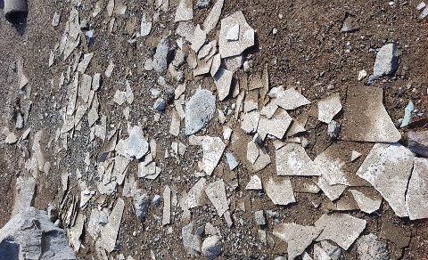 ASBESTPLATER: Det ligger et betydelig antall asbestplater i skråning ned mot fjorden, og på selve fjordbunnen, utenfor Strandefjorden Panorama. Nå skal det fjernes.