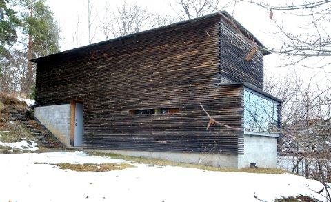 Usjenert tun: Annekset fungerer også som en skjerm mot utbyggingen av Hvamodden. Fasaden er kledd i gran behandlet med jernvitriol.