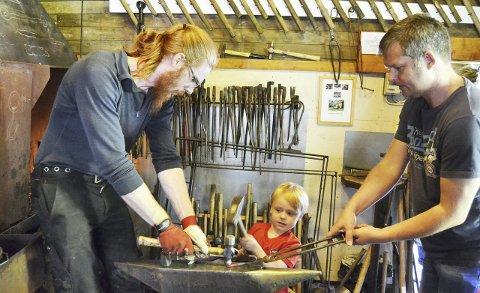 Solid grep: Markus Hamstad (4) hadde eit solid grep om hammaren medan han smidde seg krok. Pappa Roger Hamstad (t.h) og smeden Magnus Øye passer på at det går trygt føre seg.