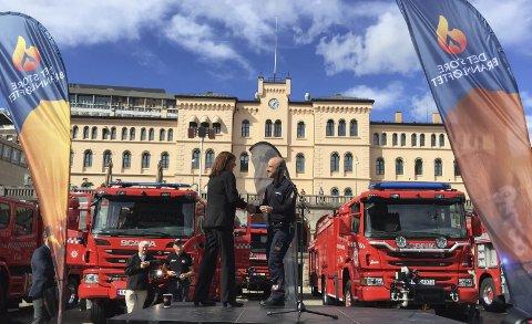 NØKKEL: Brannsjef Sturla Bråten tar imot nøkkelen til den nye brannbilen av administrerende direktør Unn Dehlen i Gjensidigestiftelsen. Justisminister Anders Anundsen var også til stede under overrekkelsen av de 36 bileneFoto: brannvesenet