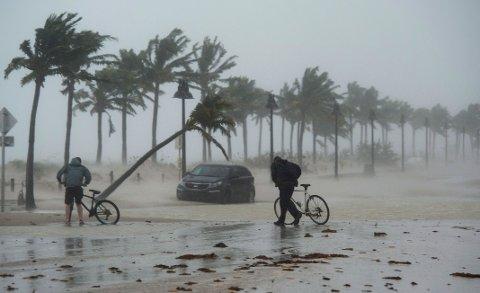 To menn går med syklene sine ved Fort Lauderdale i Florida mens orkanen Irma fortsetter videre gjennom delstaten. Foto: Paul Chiasson / AP / NTB scanpix