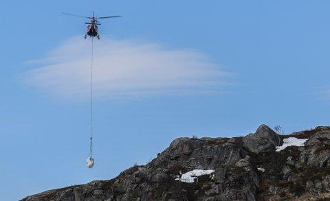 UTSTYR: Her frakter et helikoter, rekvirert av vegvesenet, utstyr for å få steinblokka ned fra fjellet. I fjellsiden skimtes mannskap ved den aktuelle steinen.