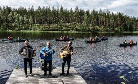 IDYLLISK: Fra venstre Kåre Erling Fjell, aLsse Johansen og Sigbjørn Rundberget på brygga med sang og spill mens deltakerne i kulturpadlingene dro forbi på Kynna.