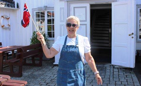 – Jeg tar fram flagget for at vi holder åpent igjen på Victoria Gestgiveri etter to uker med stengte dører på grunn av smitte blant ansatte, sier Rigmor Thorsnes. Hun er mamma til daglig leder Andreas Kristiansen.