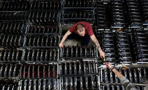 Her jobber en ansatt på Bitminer Factory i Firenze i Italia, en fabrikk som jobber med å fremstille Bitcoin. Foto: REUTERS/Alessandro Bianchi