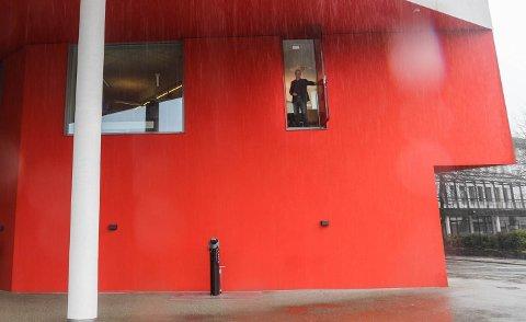 RAUD DØR: Olve Grotle stiller modig opp på bilde med den raude døra, trass i høgdeskrekken.