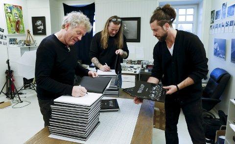 Signering:  Øyvind Staveland (til v). og Bjørn Berge signerer bøker under oppsyn av fotograf Edgar G. Bachel. Foto:  Alf-Robert Sommerbakk