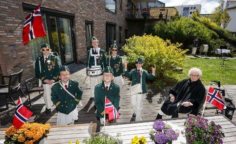 JUBILEUM: 110-årsjubilant Moss Skolemusikkorps spilte i bakhagen på Skoggata bo- og servicesenter 17. mai 2020. Beboer Berit Dahl (til høyre) koste seg med musikken i sola.