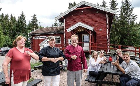 LØSER SEG: Thea Mannsee, i midten, overtar nå driften av Kafe Finnskog, og etter hvert overtar hun alt etter eierne Eva Halvorsen og Werner Stiefel. Applauderer for at kafeen lever videre gjør fra venstre ved bordet: Ane-Ingeborg Sandnæs i Visit Kongsvinger-regionen, daglig leder i Solør Næringshage, Anette Strand Sletmoen, daglig leder i Finnskogen Natur&Kulturpark, Irèn Carlström og leder i utvalget for samfunnsutvikling i Åsnes, Kristian Botten Pedersen.