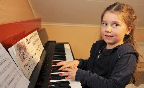 Ava (6) har akkurat startet i lære på pianoet, og lærer både bokstaver og noter samtidig.