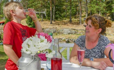 Lekker leskedrikk: Knut slukker tørsten med geitramssaften som mamma Carolina Moland har laget.I tillegg til geitramsblomster trenger du vann, sukker og sitronsyre for å produsere den vakre drikken.Foto: Mette Urdahl