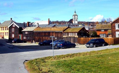 Fra bil til hus: Tomta der Larsenstuggu sto i sin tid, benyttes i dag som parkeringsplass. Nå vil Lars Sankar-Øyan sette opp igjen Larsenstuggu og uthuset som sto på tomta. Foto: Guri Jortveit