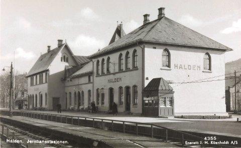 JERNBANESTASJONEN: På dette fotografiet fra 1930-tallet ser vi nærmest bygningen som var reist for Dalslandsbanen. I det lave mellombygget var det opprinnelig bl.a. dameværelse og venteværelse for 1. og 2. klasse, mens tredje klasse hadde tilhold i hovedbygningen der venteværelset fortsatt ligger. I andre etasje i hovedbygningen lå stasjonsmesterens leilighet. FOTO: NASJONALBIBLIOTEKET