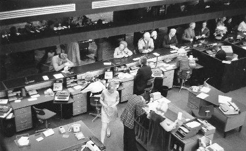 DnC 1974: Det var travelt i banken den gangen man kunne både ta ut og sette inn penger. I dag er det som kjent nokså annerledes, men det er et godt spørsmål om all framgang er til det beste for eldre bankkunder?