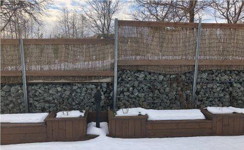 Naboene er uenige om denne muren med pilgjerde på toppen samsvarer med tegningen som er godkjent.