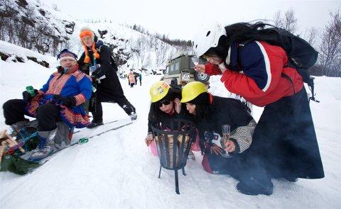 Anne Mette Gausdal, Liv Anita Østgård og Britt Johnsen prøver å få fyr på bålet under champagnelunsjen halvveis ned i løypa. Sparkekonkurransen lørdag ble en skikkelig folkefest. Foto: Ola Solvang