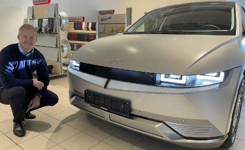 FUTURISTISK DESIGN: Nybilselger Even Rebni hos Sulland i Gjøvik lar seg lyse opp av de smale LED-lyktene på en Ioniq 5, der den på mange måter revolusjonerende bilens pussige lysstriper i underkant av «ikke-grillen» også bidrar til det futuristiske utseendet.FOTO: ØYVIN SØRAA