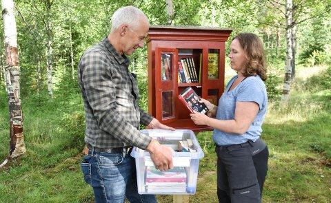 BOKSKAP: Allmenningsbestyrer Endre Jørgensen og biblioteksjef Elin Gammelmo fyller opp minibiblioteket i skogen, det første av sitt slag i Løten.