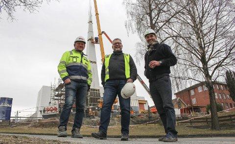 JUBEL PÅ KIRKETOMTA: Fra venstre: Prosjektleder i Tor Entreprenør Steinar Dale, kirkesjef Johannes Sørhaug og arkitekt Espen Surnevik smilte fra øre til øre da tårnet på den nye kirken var ferdig montert.