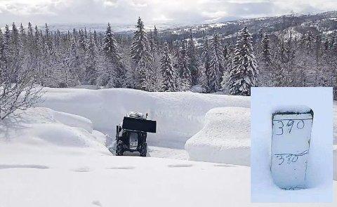Traktoren blir liten mellom snøskavlene. Innfelt målepinnen som er brukt cirka 50 høydemeter over gården.