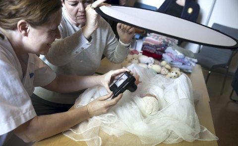 Jordmødrene får tips til hvordan de kan bruke lyset og pakke de døde babyene inn på en fin måte. Her øver de med en dukke. Foto: Monica Johansen