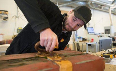 GJENBRUK: Jonas Syversen er møbelsnekker i Fredrikstad kommune. Han har fått oppgaven med å lage malen som skal brukes for å bygge nye lavetter. Sammen med kollegene på snekkerverkstedet til Etat bygg og eiendom har han plukket fra hverandre en av de gamle lavettene som brukes som modell.