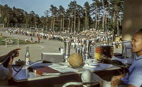 Kragerø-lekene rundt 1970: Denne store årlige håndballturneringen ble arrangert i månedsskiftet juni/juli hvert år. For mange var dette sommerens store høydepunkt. Mellom 40 og 50 lag møttes til dyst på Kragerø stadion. På dette bildet sitter en av håndballens viktige støttespillere Eivind Marthinsen. På bordet står pokalene som måtte vinnes tre ganger. Foto: Arvid Hanssen