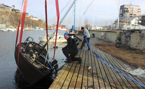 HEVET OG FJERNET: Den sunkne seilbåten ble hevet opp og fjernet fra sjøen i Kongshavn i Langesund torsdag. – Vi utfører oppdrag fra Smietangen Eiendom, sier Fredrik Hansen og Håkon Tyvold i firmaet Nordock fra Sandefjord.