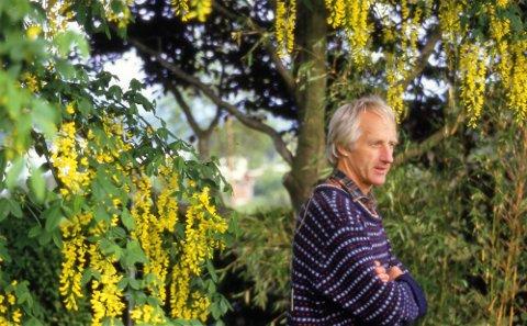 EDENS HAGE: Olav Tjore under Gullregn, ein av dei 2000 plantar, tre og vekstar i Tjorehagen.