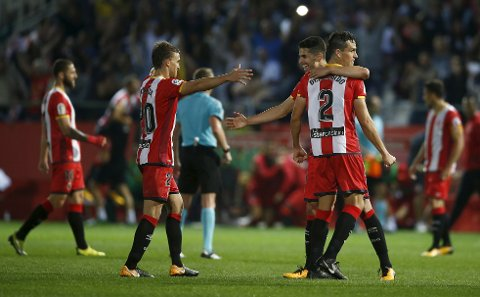 Girona's Bernardo Espinosa, (2) is hugged by teammate vÅlex Granell as they celebrate after the end of the La Liga soccer match between Girona and Real Madrid at the Montilivi stadium in Girona, Spain, Sunday, Oct. 29, 2017. Girona defeated Real Madrid 2-1. (AP Photo/Manu Fernandez)