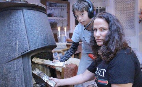 FYRER MED VED: – Ikke engang nå i november bruker vi særlig med strøm. I den delen av huset vi bruker fyrer vi med      ved. I tillegg liker jeg å bruke stearinlys i stedet for lampelys, sier Grete Solløst, og får hjelp av sønnen Sofian med vedfyringen.BILDER: SIGMUND FOSSEN