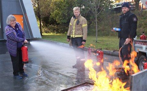 SLUKKER BRANN: Astrid Gaarder fra Brandbu fikk slukke brann med brannslukkingsapparat. Det hadde hun aldri gjort før. Henning Borgli og Thor Sparby følger med.