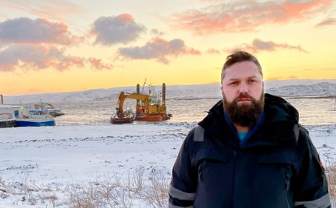 """PREGET BYGD: Havnesjef Torfinn Vassvik som selv er gamvikværing, forteller om ei preget bygd. I bakgrunnen mudringsfartøyet """"Berghavn"""" og lekteren der dødsulykka skjedde. Til venstre ser man litt av Gamvik Seafood."""