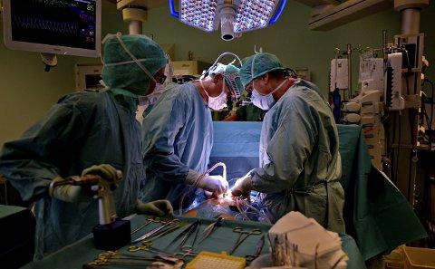 Arbeidsplassen: Kjell Saatvedt (i midten) kan stå opp til ti timer av gangen, rett opp og ned, og operere. Her er han i ferd med hjertet til Jeanette Fredriksen fra Kongsberg. En skjebnedag for pasienten, men en helt normal del av arbeisdagen for kirurgen fra Flesberg.